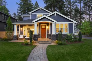 Beautiful blue craftsman style home exterior at dusk showcasing Bellevue WA homes for sale